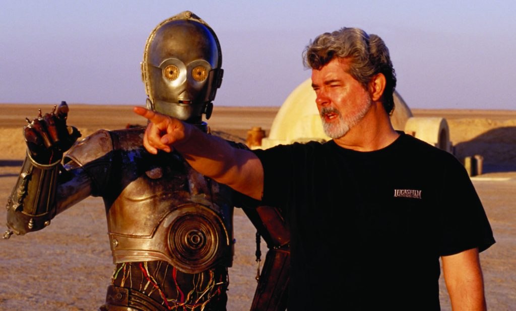 "** FILE ** In this undated publicity photo released by Lucasfilm Ltd. & TM, director George Lucas directs actor Anthony Daniels, who plays the robot C-3PO, in ""Star Wars II: Attack of the Clones,"" on location in the Tunisian desert. Dozens of groundbreaking technologies were developed for the production of the Star Wars movies. ThereÕs no mistaking the similarities. A childhood on a dusty farm, a love of fast vehicles, a rebel who battles an overpowering empire, George Lucas is the hero he created, Luke Skywalker. (AP Photo/Lucasfilm Ltd. & TM, LisaTomasetti)"