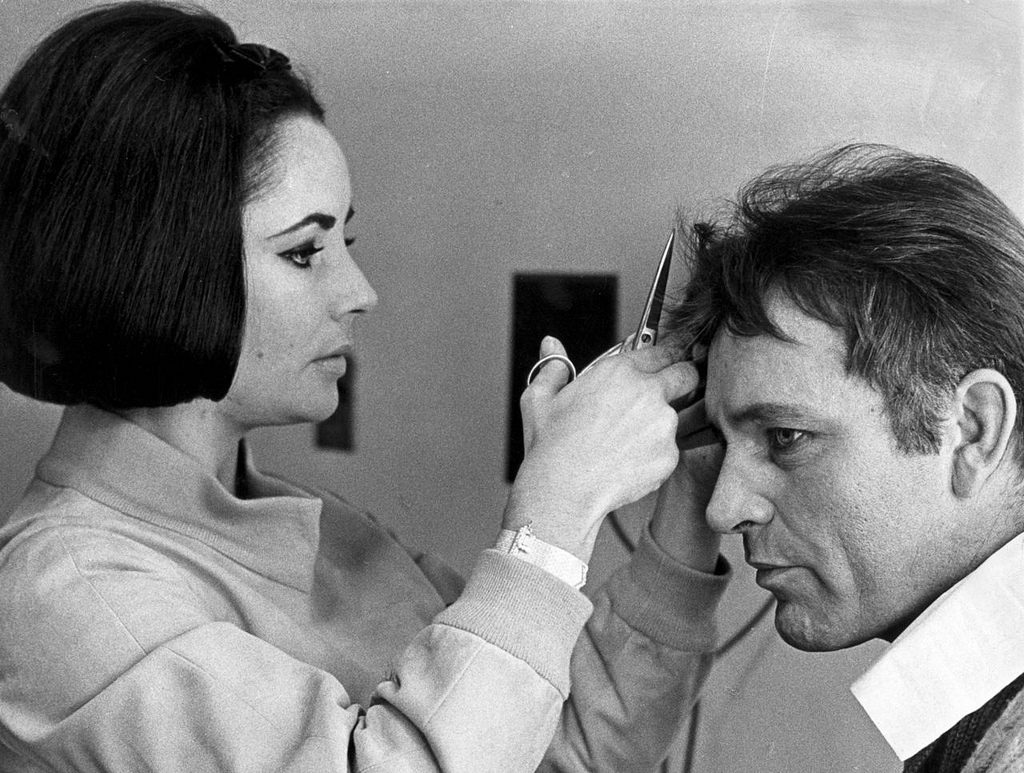 6th March 1964: Elizabeth Taylor gives her future husband Richard Burton (1925-1984) a cursory haircut with a pair of scissors. (Photo by William Lovelace/Express/Getty Images)