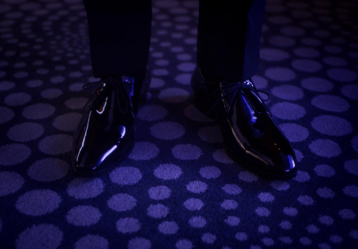 Bir adamın siyah rugan ayakkabıları var.