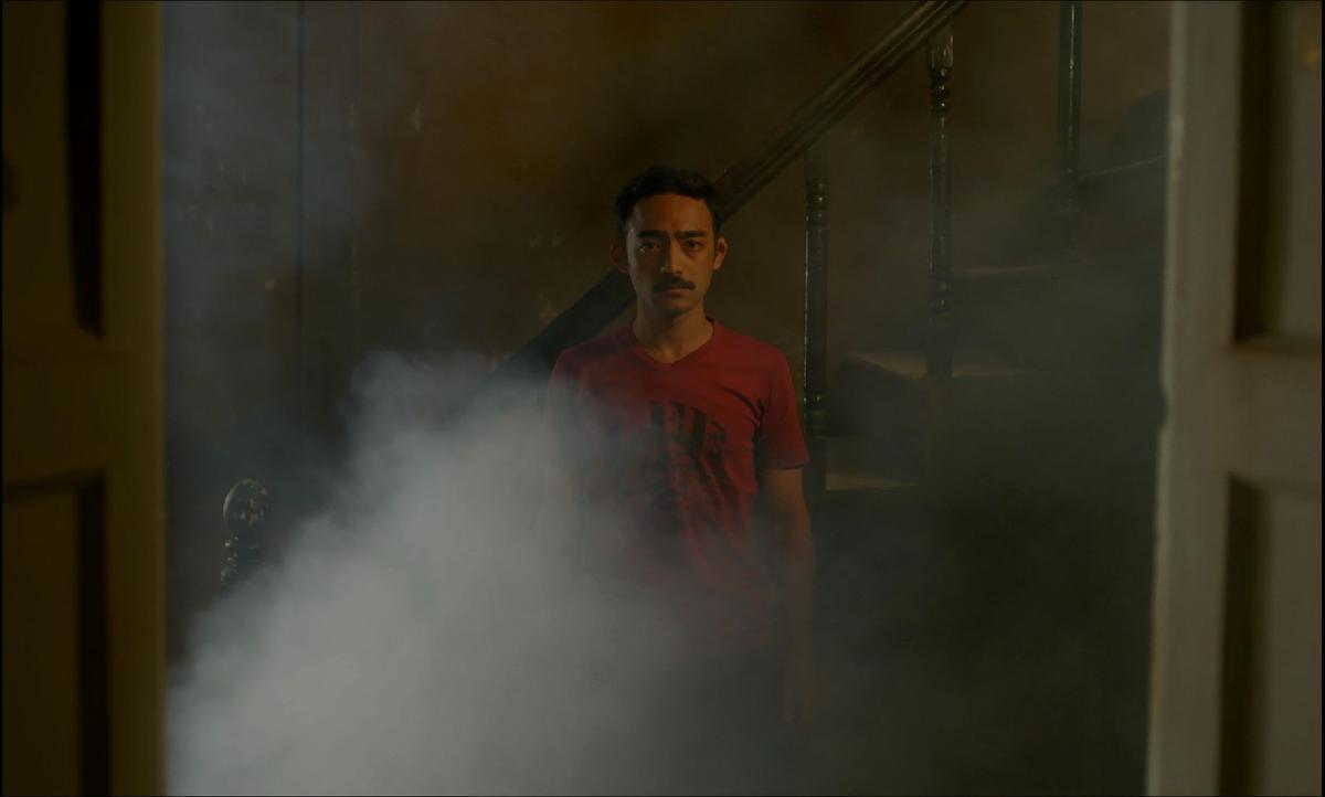 Merdiven önünde bir adam dumanlar arasından kameraya bakıyor.