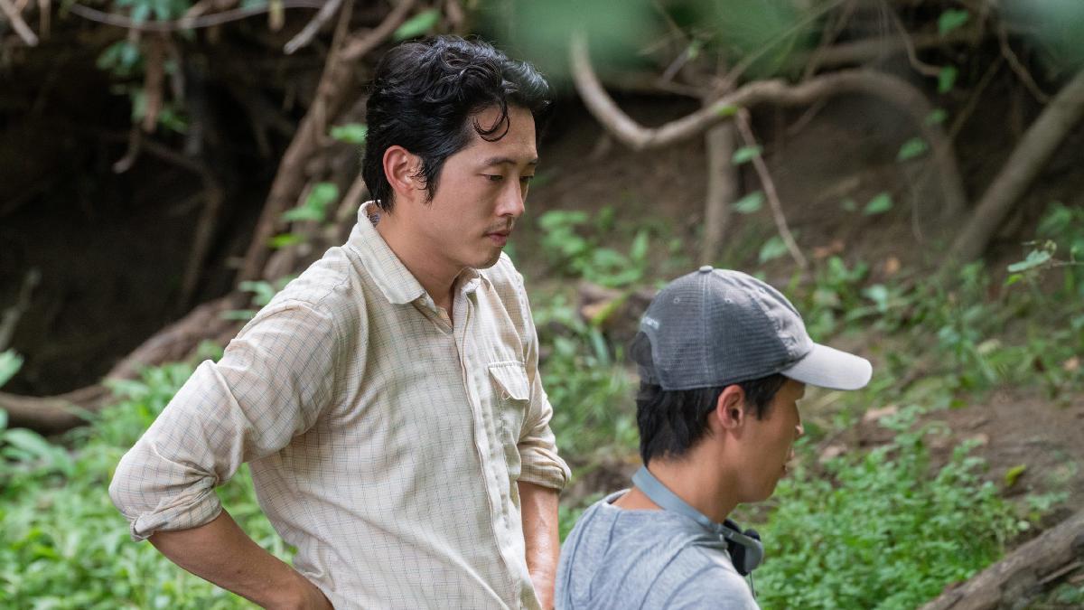 İki adam ormanlık bir alanda. Sağdaki kasket takıyor. Soldaki onu dinliyor.