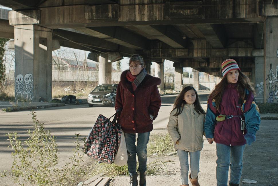 2 kadın ve bir çocuk köprünün altından yürüyor.
